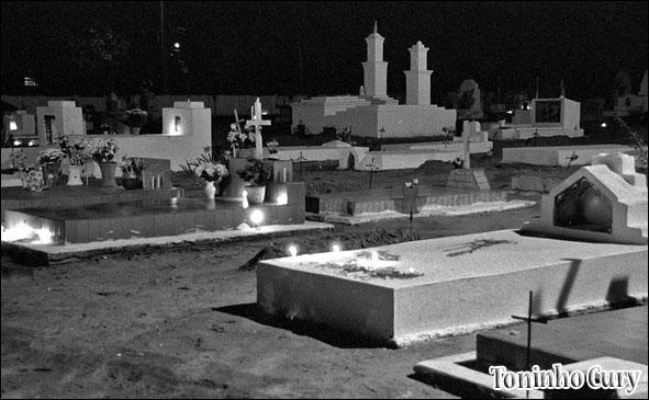 Os túmulos do cemitério de Ubarana recebem velas na noite de Todos os Santos. Novembro/1999. (Foto: Toninho Cury)